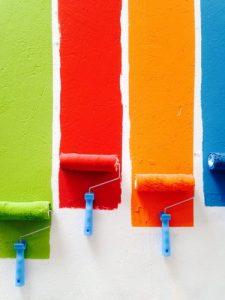 pinceles rodillo pintando con colores sobre pared blanca