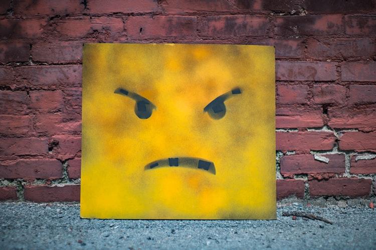 cartel amarillo con cara enojada