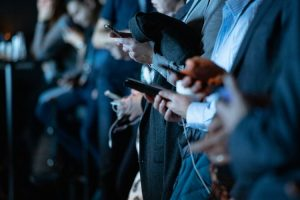 personas de traje usando sus celulares
