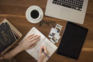 persona escribiendo en anotador, taza de cafe, fotos, anteojos y compuadora
