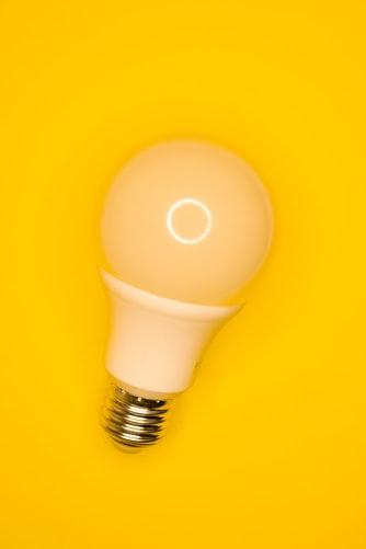 foco de luz sobre fondo amarillo. imagen ilustrativa de idea
