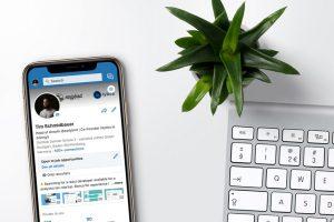 celular mostrando aplicacion de linkedin, teclado y plantin