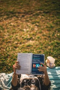 mujer leyendo libro de marketing digital. conceptos básicos del marketing digital
